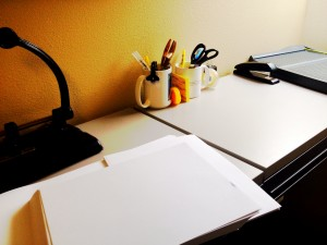Photo of office workspace with paper, pens, etc.