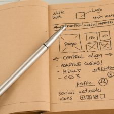 Photo of notebook with website wireframe